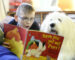 GLASGOW, SCOTLAND - DECEMBER 11: Langfaulds Primary pupil Reece Cameron (P7) reads to Willow the dog as part of supported reading at the school with dogs from Therapet on December 11, 2017 in Glasgow, Scotland. Shot for a Christmas box feature for the Evening Times by Catriona Stewart (Photo by Jamie Simpson/Herald & Times) - JS
